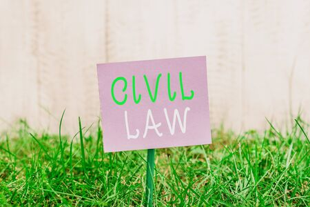 Writing note showing Civil Law. Business concept for Law concerned with private relations between members of community Plain paper attached to stick and placed in the grassy land