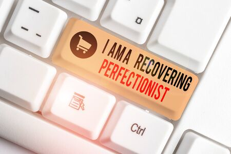 Text sign showing I Am A Recovering Perfectionist. Business photo showcasing Obsessive compulsive disorder recovery White pc keyboard with empty note paper above white background key copy space Фото со стока
