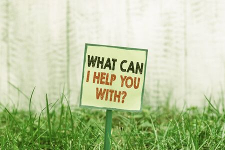 Conceptual hand writing showing What Can I Help You With Question. Concept meaning Offering assistance Experts advice ideas Plain paper attached to stick and placed in the grassy land