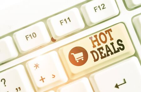 Text sign showing Hot Deals. Business photo text An agreement through which one of the paties is offered and accept White pc keyboard with empty note paper above white background key copy space