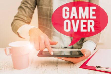 Text sign showing Game Over. Business photo showcasing A situation in a particular sport that reach his finals or ending Business woman sitting with mobile phone and cup of coffee on the table