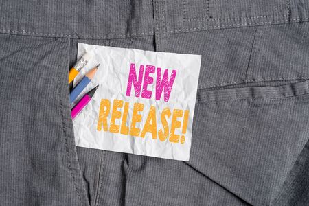 Text sign showing New Release. Business photo showcasing announcing something newsworthy recent product Writing equipment and white note paper inside pocket of man work trousers