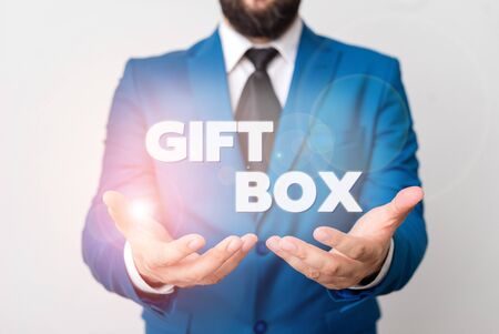 Text sign showing Gift Box. Business photo showcasing A small cointainer with designs capable of handling presents Man with opened hands in fron of the table. Mobile phone and notes on the table