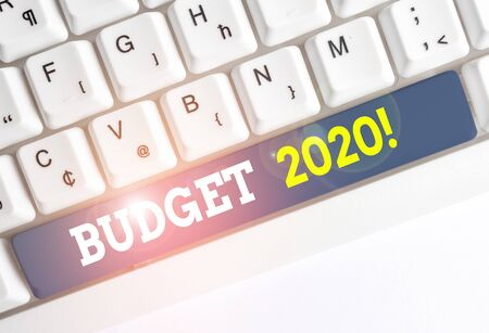 Conceptual hand writing showing Budget 2020. Concept meaning estimate of income and expenditure for next or current year White pc keyboard with note paper above the white background
