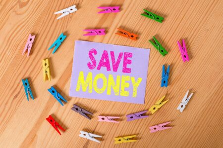 Handwriting text Save Money. Conceptual photo store some of your cash every month to use them sometime later Colored clothespin papers empty reminder wooden floor background office