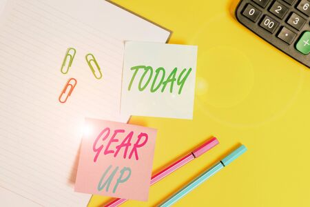 Text sign showing Gear Up. Business photo showcasing Asking someone to put his clothes or suit on Getting ready fast Empty blue paper with copy space paper clips and pencils on the yellow table