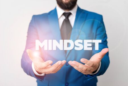 Text sign showing Mindset. Business photo showcasing A standard thought of a demonstrating of what he orshe will be done Man with opened hands in fron of the table. Mobile phone and notes on the table Standard-Bild