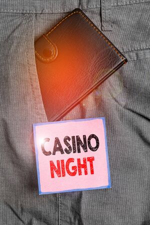 Handwriting text writing Casino Night. Conceptual photo event where can experience the fun playing in a real casino Small little wallet inside man trousers front pocket near notation paper