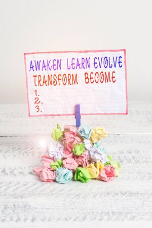 Conceptual hand writing showing Awaken Learn Evolve Transform Become. Concept meaning Inspiration Motivation Improve Reminder pile colored crumpled paper clothespin wooden space