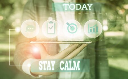 Text sign showing Stay Calm. Business photo showcasing Maintain in a state of motion smoothly even under pressure Female human wear formal work suit presenting presentation use smart device