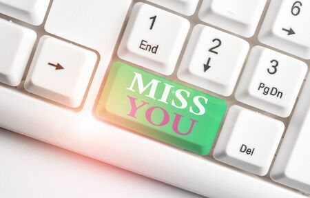 Text sign showing Miss You. Business photo showcasing Longing for an important demonstrating in your life for a period of time White pc keyboard with empty note paper above white background key copy space