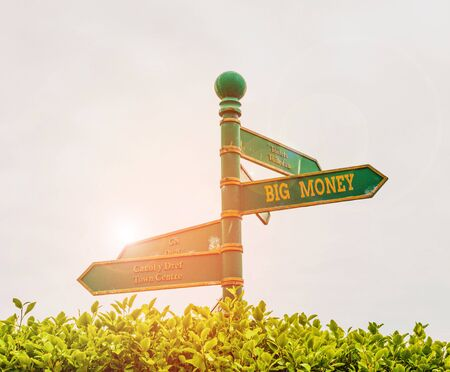 Handwriting text Big Money. Conceptual photo Pertaining to a lot of ernings from a job,business,heirs,or wins Green road sign on the crossroads with blue sky and green grass in the background 写真素材