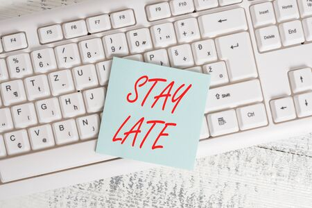 Conceptual hand writing showing Stay Late. Concept meaning A routine in which a demonstrating goes to somewhere out of time Keyboard office supplies rectangle shape paper reminder wood