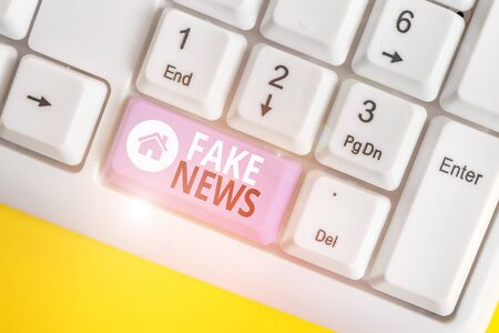 Word writing text Fake News. Business photo showcasing Giving information to showing that is not true by the media White pc keyboard with empty note paper above white background key copy space