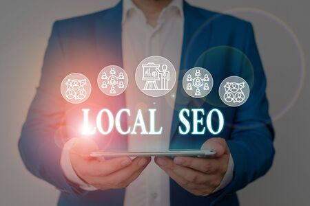 Writing note showing Local Seo. Business concept for This is an effective way of marketing your business online Male wear formal work suit presenting presentation smart device