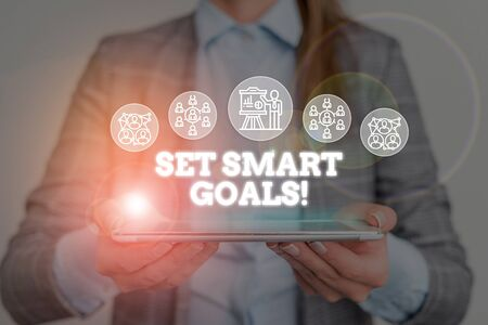 Conceptual hand writing showing Set Smart Goals. Concept meaning list to clarify your ideas focus efforts use time wisely Woman wear work suit presenting presentation smart device