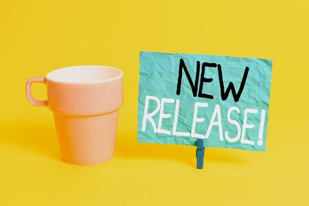 Handwriting text New Release. Conceptual photo announcing something newsworthy recent product Cup empty paper blue clothespin rectangle shaped reminder yellow office Stock fotó - 131605498