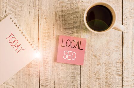 Conceptual hand writing showing Local Seo. Concept meaning This is an effective way of marketing your business online Stationary placed next to a coffee cup above wooden table