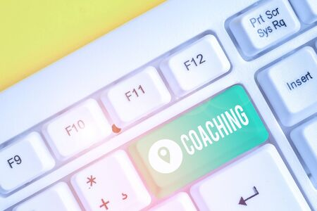 Text sign showing Coaching. Business photo text demonstrating supports client in achieving specific demonstratingal goal White pc keyboard with empty note paper above white background key copy space