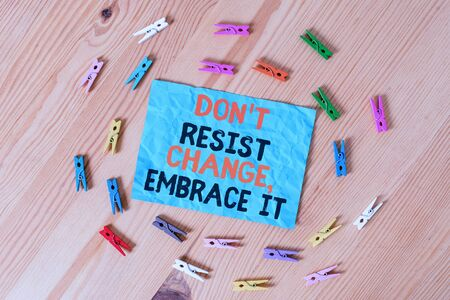 Word writing text Don T Resist Change Embrace It. Business photo showcasing Be open to changes try new things positive Colored clothespin papers empty reminder wooden floor background office