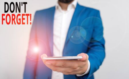 Word writing text Don T Forget. Business photo showcasing used to remind someone about important fact or detail Business concept with man holding mobile phone with touch screen Stock Photo