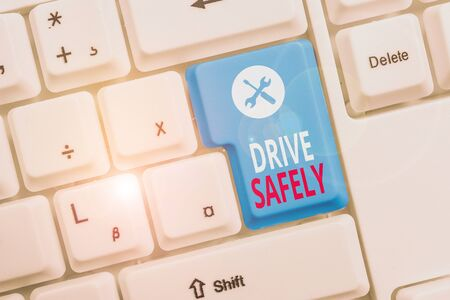 Conceptual hand writing showing Drive Safely. Concept meaning you should follow the rules of the road and abide laws Keyboard with note paper on white background key copy space 스톡 콘텐츠