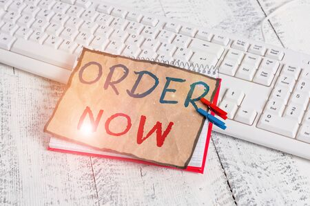Text sign showing Order Now. Business photo text service restaurants or stores provide to get what you need home notebook paper reminder clothespin pinned sheet white keyboard light wooden Imagens
