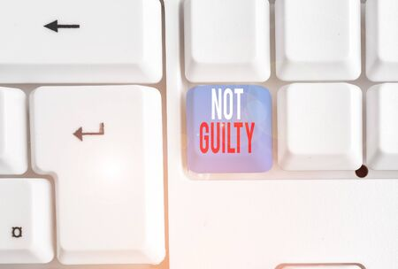 Handwriting text writing Not Guilty. Conceptual photo someone is innocent didnt commit specific crime He free White pc keyboard with empty note paper above white background key copy space
