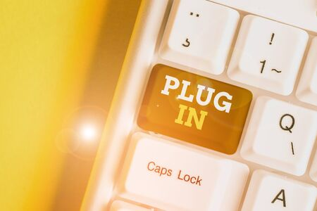 Text sign showing Plug In. Business photo text putting device into electricity to turn it on Power it Connecting White pc keyboard with empty note paper above white background key copy space