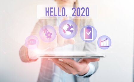 Conceptual hand writing showing Hello 2020. Concept meaning expression or gesture of greeting answering the telephone Female human wear formal work suit presenting smart device