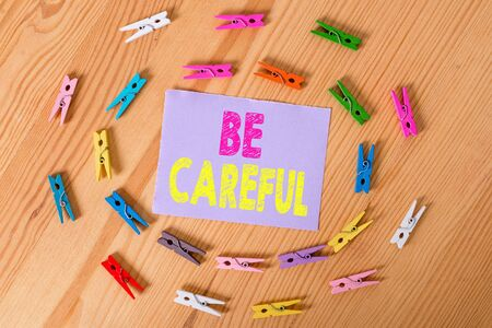 Handwriting text Be Careful. Conceptual photo making sure of avoiding potential danger mishap or harm Colored clothespin papers empty reminder wooden floor background office