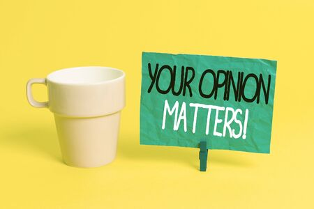 Handwriting text Your Opinion Matters. Conceptual photo show you do not agree with something that just been said Cup empty paper blue clothespin rectangle shaped reminder yellow office