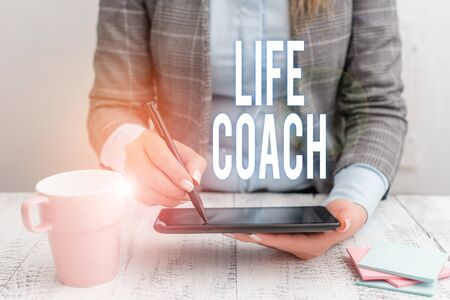 Writing note showing Life Coach. Business concept for A demonstrating who advices clients how to solve their problems or goals Business woman sitting with mobile phone and cup of coffee on the table Banco de Imagens