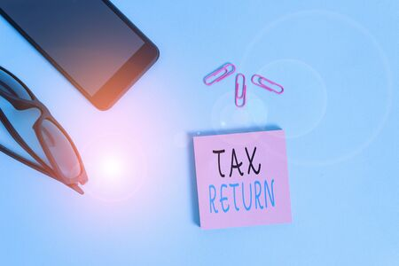 Conceptual hand writing showing Tax Return. Concept meaning which taxpayer makes annual statement of income circumstances Eyeglasses colored sticky note smartphone pastel background Banco de Imagens