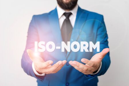 Text sign showing Iso Norm. Business photo showcasing An accepted standard or a way of doing things most showing agreed Man with opened hands in fron of the table. Mobile phone and notes on the table