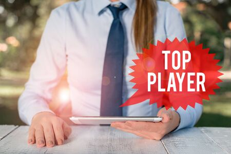 Word writing text Top Player. Business photo showcasing being best in sports game like football or electronic ones Female business person sitting by table and holding mobile phone 版權商用圖片