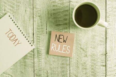 Conceptual hand writing showing New Rules. Concept meaning A state of changing an iplemented policy for better upgrade Stationary placed next to a coffee cup above wooden table