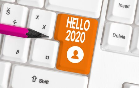 Conceptual hand writing showing Hello 2020. Concept meaning expression or gesture of greeting answering the telephone White pc keyboard with note paper above the white background