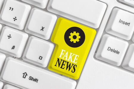 Conceptual hand writing showing Fake News. Concept meaning Giving information to showing that is not true by the media White pc keyboard with note paper above the white background