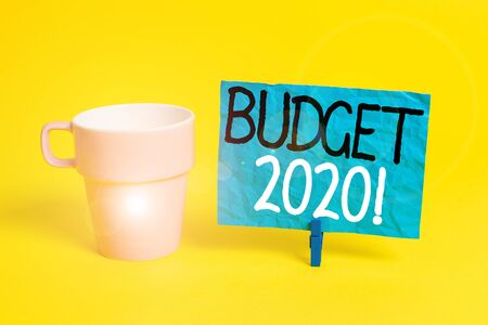 Handwriting text Budget 2020. Conceptual photo estimate of income and expenditure for next or current year Cup empty paper blue clothespin rectangle shaped reminder yellow office