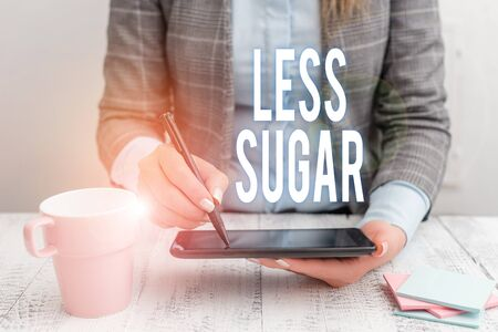 Writing note showing Less Sugar. Business concept for Lower volume of sweetness in any food or drink that we eat Business woman sitting with mobile phone and cup of coffee on the table