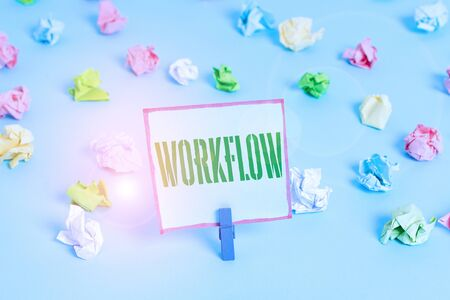 Word writing text Workflow. Business photo showcasing Continuity of a certain task to and from an office or employer Colored crumpled papers empty reminder blue floor background clothespin