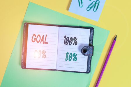 Conceptual hand writing showing Goal 100 Percent 90 Percent 80 Percent. Concept meaning Percentage of your objectives fulfilment success level Locked diary striped sheets clips notepad colored background