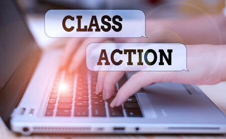 Writing note showing Class Action. Business concept for lawsuit filed by small group acting on behalf of a large group woman with laptop smartphone and office supplies technology