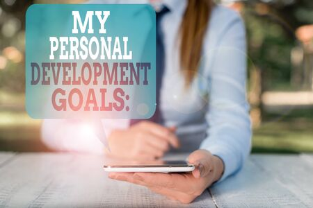 Writing note showing My Personal Development Goals. Business concept for Desires Wishes Career Business planning Female business person sitting by table and holding mobile phone