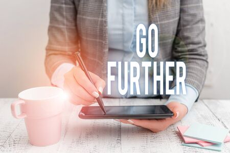 Writing note showing Go Further. Business concept for To move to a greater distance or overcome your limitations Business woman sitting with mobile phone and cup of coffee on the table Stockfoto