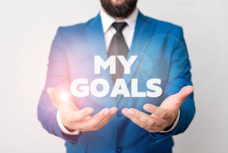 Text sign showing My Goals. Business photo showcasing Future or desired result that a demonstrating commits to achieve Man with opened hands in fron of the table. Mobile phone and notes on the table