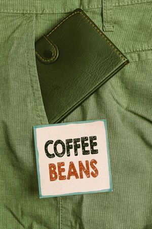 Handwriting text writing Coffee Beans. Conceptual photo pit inside the red or purple fruit often referred as a cherry Small little wallet inside man trousers front pocket near notation paper Stockfoto