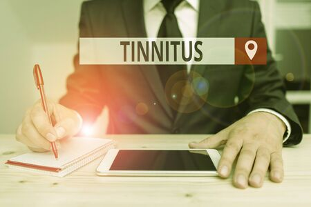 Writing note showing Tinnitus. Business concept for A ringing or music and similar sensation of sound in ears