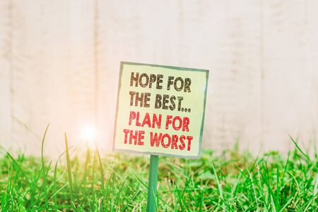 Conceptual hand writing showing Hope For The Best Plan For The Worst. Concept meaning Make plans good and bad possibilities Plain paper attached to stick and placed in the grassy land